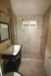 Bathroom featuring a view of the sink, mirror, travertine tile shower, light fixture.